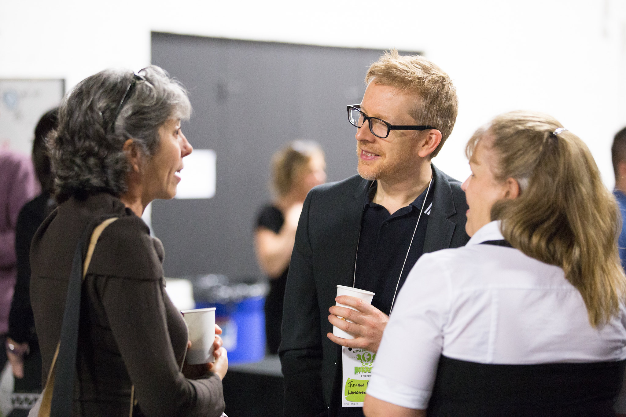 Group of three people at a conference talking informally